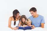 Family sitting with a storybook on the bed