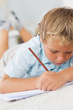 Boy writing lying on the floor