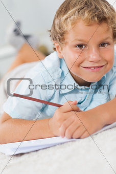 Smiling boy writing lying on the floor