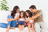 Smiling family using a digital tablet