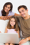 Smiling family using the laptop