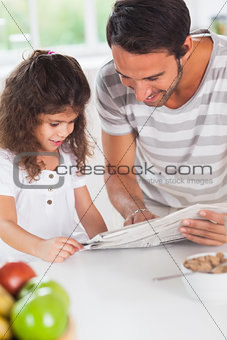 Dad and daughter reading a newspaper