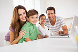 Happy family looking at the camera with a laptop