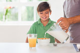 Father putting milk in the cereal of his son