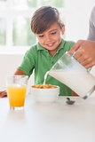 Father pouring milk in the cereal of his son