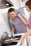 Woman getting man to taste dinner