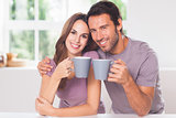 Couple looking at the camera with a coffee