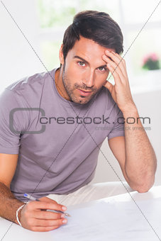 Man doing his accounting and looking at camera