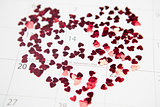 Pink confetti scattered in heart shape over valentines day