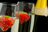 Strawberries floating in two champagne flutes