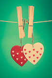 Two heart ornaments hanging from pegs on a line
