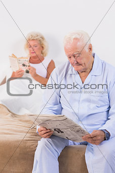 Aged couple reading on the bed