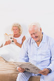 Smiling elderly couple reading on the bed