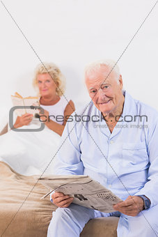 Old persons looking at camera while reading