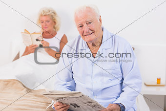 Aged couple looking at camera while reading