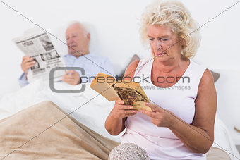Aged couple reading a book and newspaper