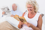 Old couple reading book and newspaper