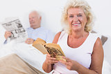 Smiling old couple reading book and newspaper