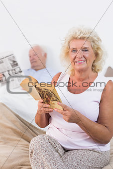 Smiling aged couple reading book and newspaper