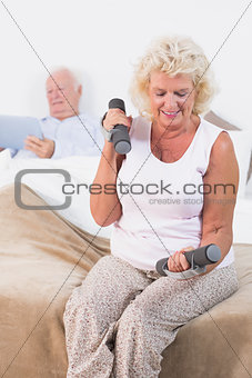 Aged woman lifting hand weights