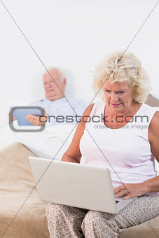 Old couple using a tablet and the laptop