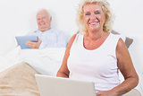 Smiling aged couple using a tablet and the laptop