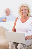 Happy aged couple using a tablet and the laptop