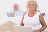 Smiling old couple using a tablet and the laptop