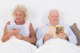 Old couple reading and using a tablet pc