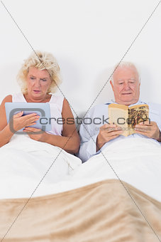 Old couple reading or using a digital tablet