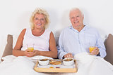 Aged couple eating breakfast