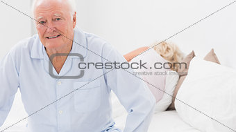 Old man sitting while woman sleeping