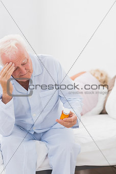 Old man holding pills