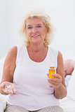Calm aged woman with the opened pill bottle