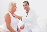 Smiling doctor examining an old woman