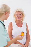 Nurse talking about a pill bottle to her smiling patient
