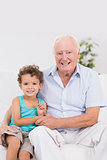 Happy grandfather and grandson sitting on the sofa