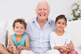 Grandfather and children sitting on the sofa