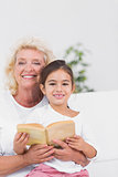 Smiling granddaughter and grandmother reading a novel together