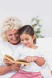 Cheerful granddaughter and grandmother reading a novel together
