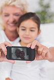 Cheerful granddaughter and grandmother taking photos