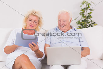 Aged couple using a laptop and the tablet