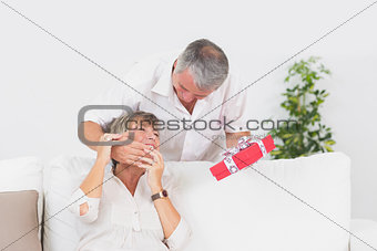 Old man hiding eyes his wife to give a gift