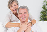 Old couple smiling at the camera and hugging