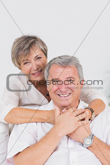 Old lovers smiling at the camera and hugging