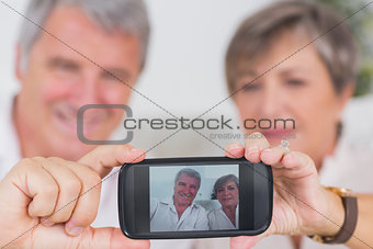 Old couple taking a picture of themselves
