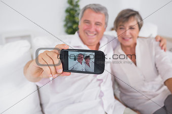 Old man taking a photo of him and his wife