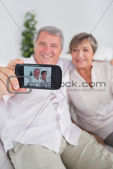 Old man taking a picture of him and his wife