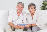 Old couple looking camera with tablet pc