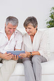 Old couple looking tablet pc with smiling